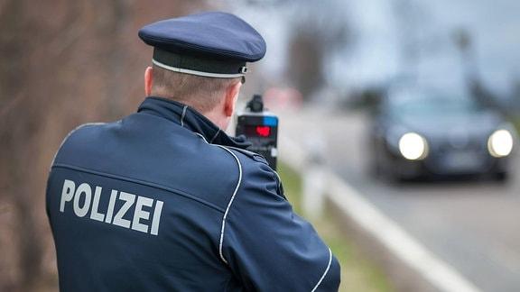 Ein Polizist misst mit einem Lasermessgerät die Geschwindigkeit von Autofahrern