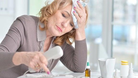 Eine offensichtlich kranke Frau wählt eine Rufnummer mit dem Telefon