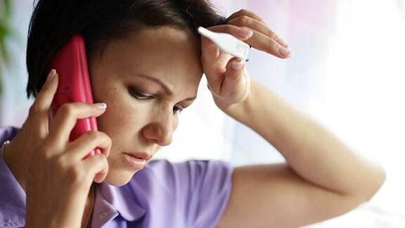 Eine Frau mit einem Fieberthermometer inder Hand, die einen Anruf tätigt.