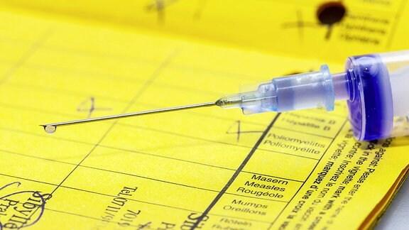 Eine Spritze liegt auf einem Impfpass.