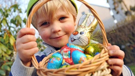 Ein Junge hält ein Körbchen mit Ostersüßigkeiten