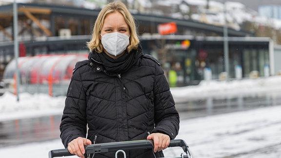 Frau mit FFP2-Maske schiebt einen Einkaufswagen.
