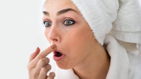 Eine junge Frau betrachtet im Spiegel erstaunt einen Pickel in ihrem Gesicht