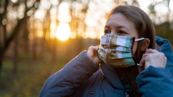 Junge Frau legt eine selbstgemachte Schutzmaske an.
