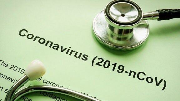 Ein Stethoskop liegt auf einem Zettel mit der Aufschrift Coronavirus.