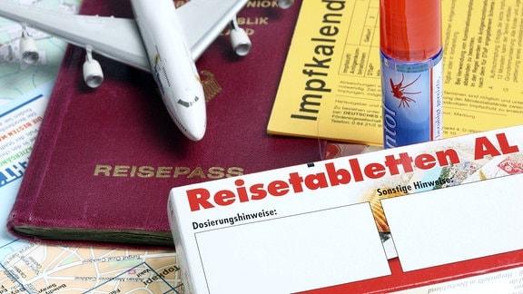 Impfausweis, Reisepass, Reisetabletten, Spielzeugflugzeug