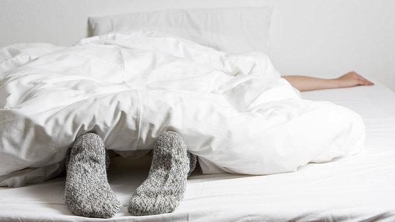 Eine junge Frau liegt im Bett, die Füsse in warmen Wollsocken