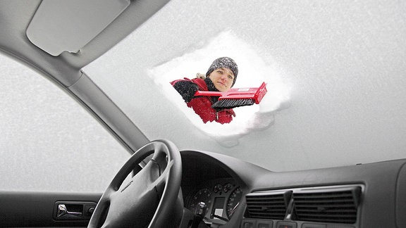 Frau entfernt im Winter Schnee und Eis von der Windschutzscheibe eines tief eingeschneiten Autos.