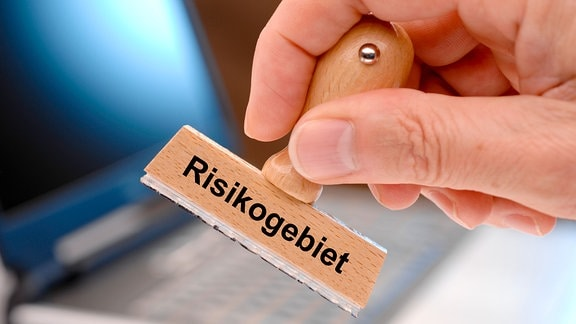 Aufdruck 'Risikogebiet' auf Holzstempel