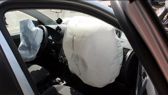Blick in ein Unfallauto. Die Airbag haben sich geöffnet. Der Airbag auf der Fahrerseite ist bereits wieder zusammengefallen, der auf der Beifahrerseite ist noch prall gefüllt.
