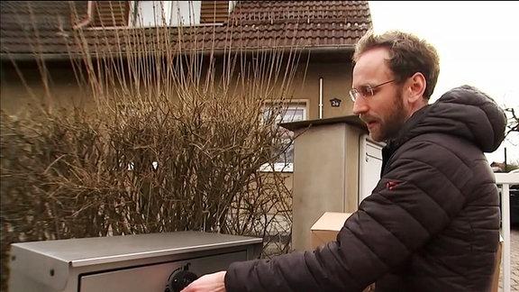 Ein Mann öffnet eine neu erfundene Paketbox
