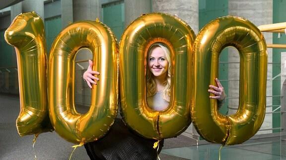 """Moderatorin Henriette Fee Grützner mit einer """"1000"""" aus goldfarbenen Ballons"""