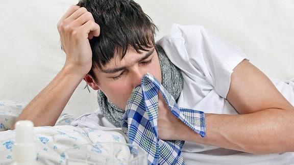 Ein junger Mann liegt im Bett und hält sich ein Taschentuch vor den Mund