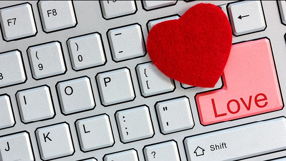 Ein rotes Herz liegt auf einer Tastatur, auf deren rosa Enter-Taste das Wort Love steht