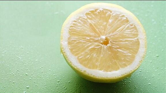 Eine Zitronenhälfte im Anschnitt vor grünem Hintergrund.