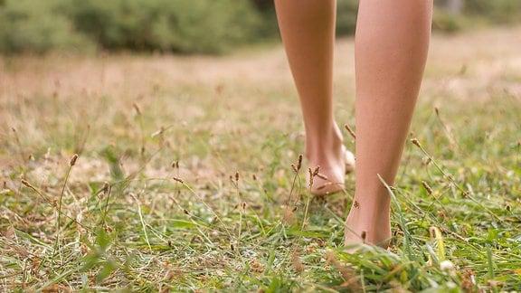 Die Füße einer barfuß über einen Rasen laufenden Frau.