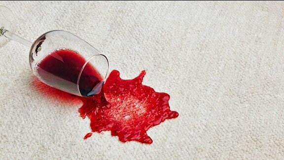 Ein umgekipptes Rotweinglas auf einem hellen Teppich