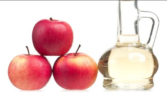 Eine Karaffe mit Essig neben drei Äpfeln.