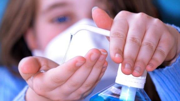 Eine Frau mit Mundschutz desinfiziert ihre Hände