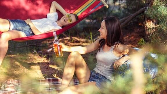 Eine junge Frau mit Hut sitzt in der Sonne