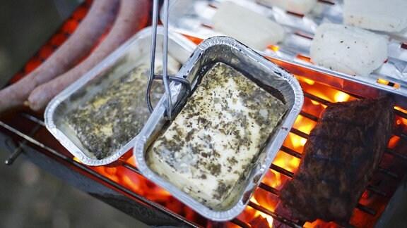Grillkäse in Aluschale auf einem Grill