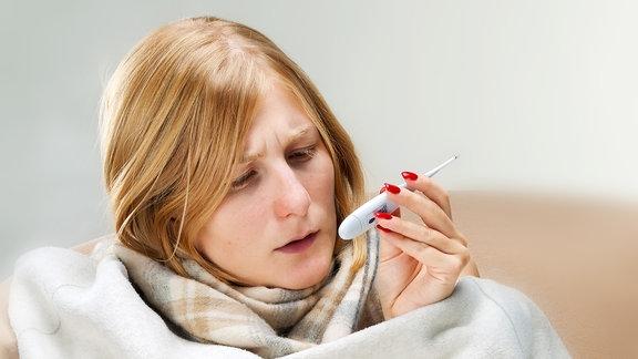 Eine junge Frau sitzt, in Decken eingewickelt, auf einem Stuhl und liest von einem Fieberthermometer die Temperatur ab