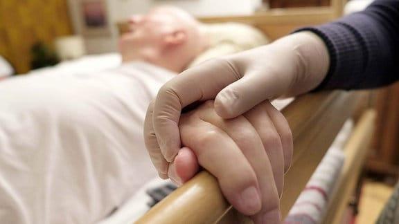 Eine in einem Gummihandschuh steckende Hand hält die Hand eines Mannes, der pflegebedürftig im Bett liegt.