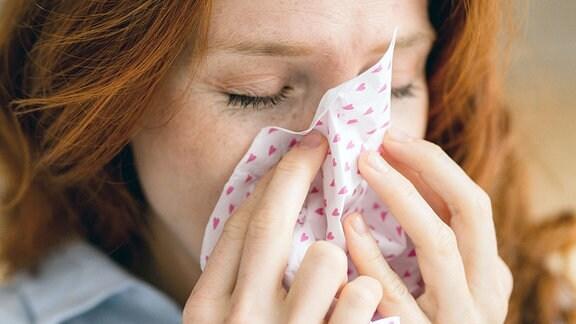 Eine Frau schnaubt sich die Nase.