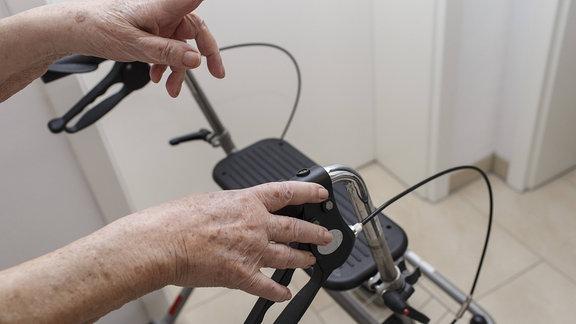 Hände einer Patientinan einem Rollator