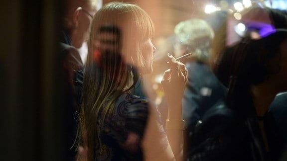 Besucher eines Theaters, während einer Raucherpause.