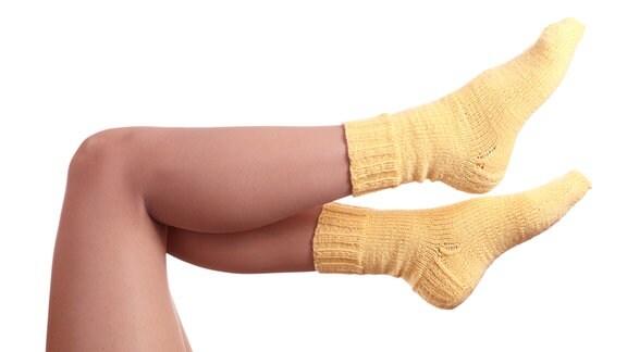Frauenbeine, an den Füßen gelbe Socken
