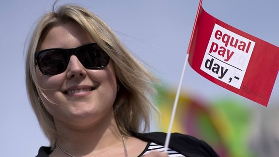 "Demonstrantin mit Fahne ""Equal Pay Day""."