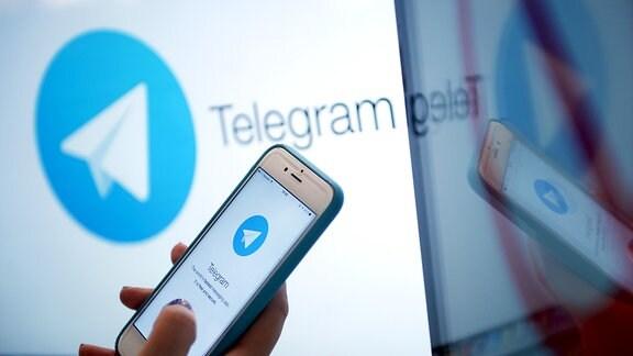 """Smartphone mit geöffneter App """"Telegram"""" vor PC-Bildschirm mit Telegram-Schriftzug."""