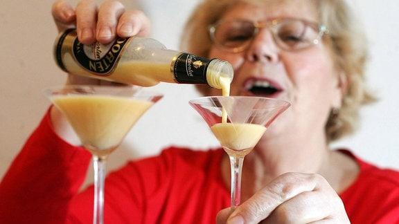 Rentnerin gießt fröhlich Eierlikör in zwei Gläser .