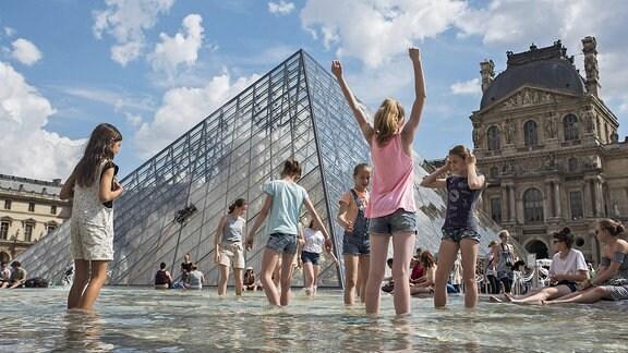 Menschen an einem Springbrunnen vor dem Louvre
