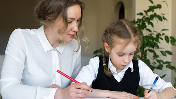 Eine Schülerin macht am Schultisch ihre Schulaufgaben, während eine junge Frau die Arbeit korrigiert.