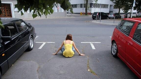 Eine Frau hält einen Parkplatz besetzt