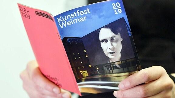 Eine Frau blättert im Programmheft für das Kunstfest Weimar 2019.