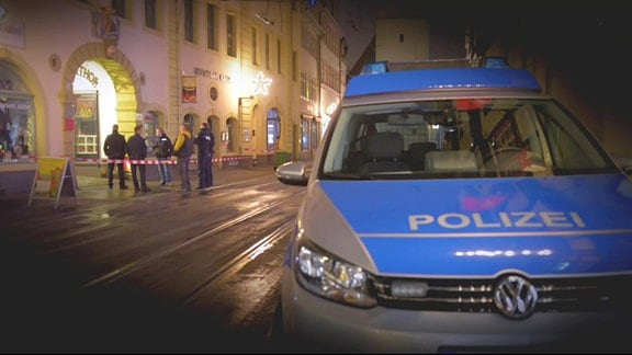 Vor einem Haus stehen Polizisten. Ein Bereich auf dem Bürgersteig ist abgesperrt. Auf der Straße steht ein Polizeiwagen.