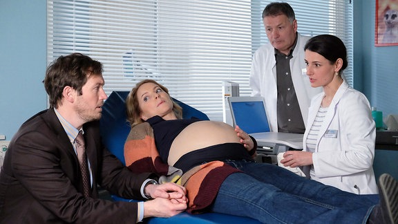 Lilly Holzer (Diana Staehly, 2.v.li.) und ihr Mann Jonas (Stefan Murr, li.) sind zur Ultraschall-Untersuchung ihrer Drillinge in der Sachsenklinik. Lilly ist in der 33. Woche und eins der Kinder wird nicht mehr ganz optimal versorgt. Dr. Maria Weber (Annett Renneberg, re.) und Dr. Roland Heilmann (Thomas Rühmann, 2.v.re.) entscheiden, die Kinder zu holen. Dabei wird klar, dass Jonas von der vorangegangenen wirklich riskanten OP in Lillys Bauch nichts wusste.