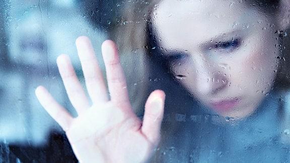 Eine junge Frau schaut traurig durch eine regennasse Fensterscheibe.
