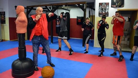 Ein Trainer zeigt beim Boxtraining einen Schlag. Mehrere Frauen und Männer in Sportkleidung machen es ihm nach