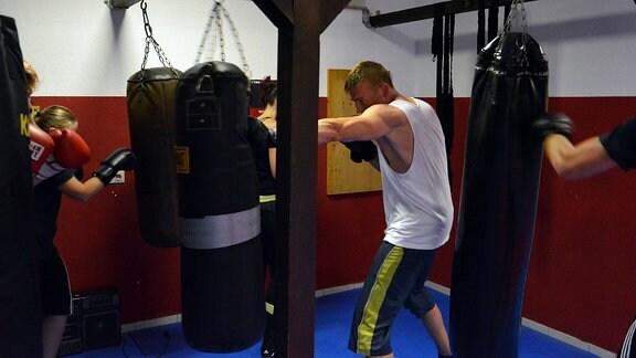 Ein Mann trainiert an einem Sandsack boxen