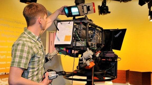 Junger Mann steht hinter einer Fernsehkamera