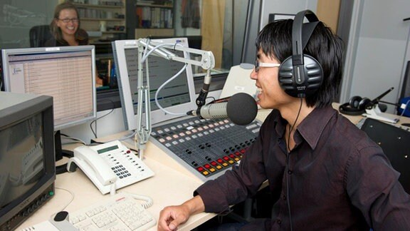 Junger Mann mit Kopfhörern sitzt in einem Studio