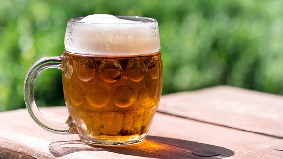 Ein Glass Bier auf einem Holztisch.