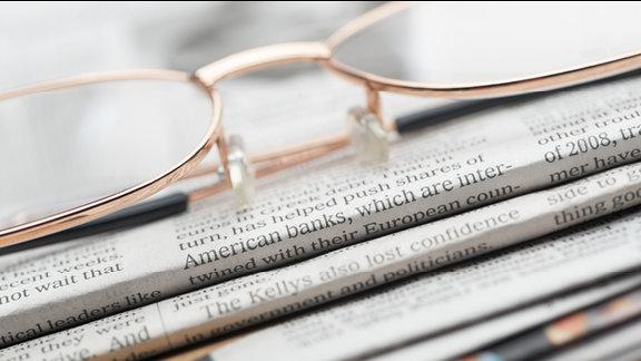 Ein Lesebrille liegt auf mehreren Zeitungen.