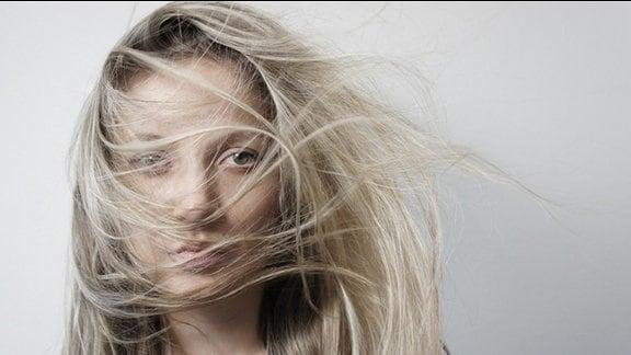 junge Frau mit blonden Haaren vor grauem Hintergund
