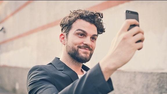 Ein Mann mit einem Smartphone mach ein Selfie