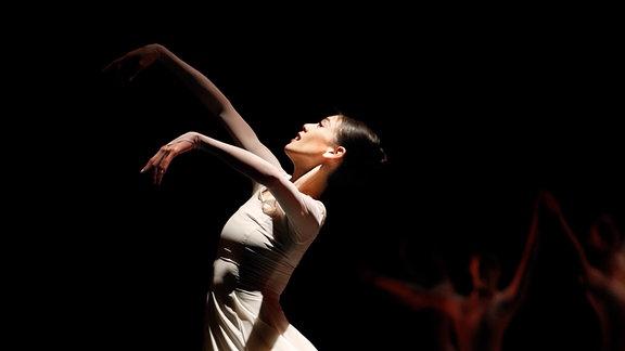 Eine Balletttänzerin anmutig auf der Bühne.